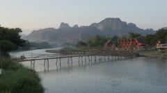 Kids on bicycle cross bamboo bridge,Vang Vieng,Laos Stock Footage