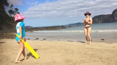 Mother and daughter play bat and ball on the beach during summer vacation Stock Footage