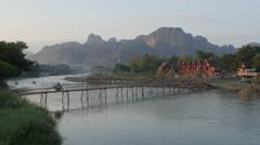 Packed motorcycle crossing bamboo bridge,Vang Vieng,Laos Stock Footage