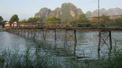 Motorcycle over and motorboat under bridge,Vang Vieng,Laos Stock Footage