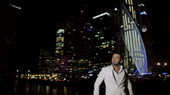 Brutal man in a white suit in the night Business Center Stock Footage