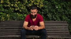Young confident bearded man using his phone and looking to the camera in a park - stock footage
