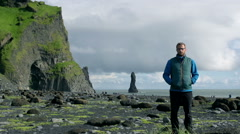 Time lapse man standing on Reynisfjara beach at south coast of Iceland at daytim Stock Footage