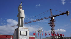 statue of Mao Zedong in front of a large construction site - stock footage