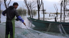 Fisherman clean the net after fishing on Erhai Lake Stock Footage