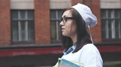 Portrait of student medical school. The girl in glasses and medical clothing Stock Footage