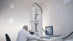 Senior scientist doing research in laboratory equipment electron microscope - stock footage