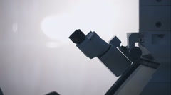Silhouette of a female researcher looking through a microscope Stock Footage