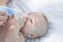 Mother using baby nasal aspirator - stock photo