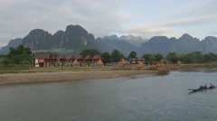 Karst mountains and bungalows with motorboat,Vang Vieng,Laos Stock Footage
