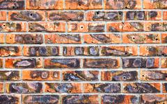Weathered stained old red brick wall as background - stock photo