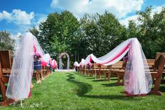 Wedding benches with flower arch for ceremony outdoors Stock Photos