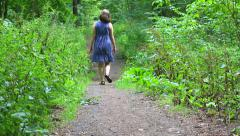 Girl in blue dress walking by forest path. Full HD Stock Footage