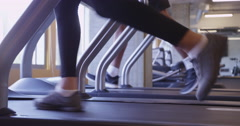 4k Close up of two people feet running on treadmill in gym low angle view Stock Footage