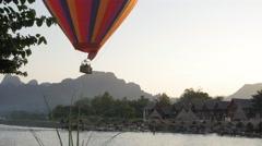 Hot air balloon rising above river bars,Vang Vieng,Laos Stock Footage