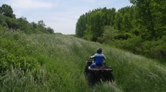 Young man driving quadbike in the forest. - stock footage