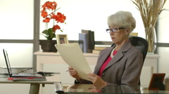 Businesswoman working on paperwork at her desk Stock Footage