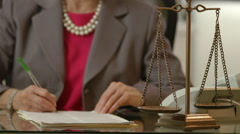 Focus on scales of justice while woman lawyer signs legal papers Stock Footage