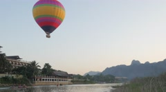 Hot air balloon above river with motorboats,Vang Vieng,Laos Stock Footage
