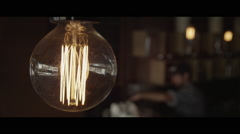 Incandescent lightbulb closeup in night cafe - stock footage