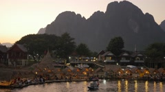 Boat transporting inner tubes in evening,Vang Vieng,Laos Stock Footage