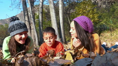 Two girls and a little handsome boy lying on fall leaves in park, dolly shot Stock Footage