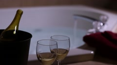 Wine in foreground with jacuzzi tub filling in background Stock Footage
