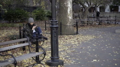 Asian girl sitting on bench on smartphone, fall day in Washington Square Park NY Stock Footage