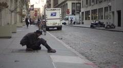 Black homeless man sitting on sidewalk while man walks past him, ignoring NYC Stock Footage