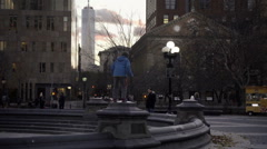 Boy climbs to top of fountain in center Washington Square Park stands proud NYC Stock Footage