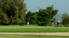 Three friends enjoy a day out on the links together. Stock Footage