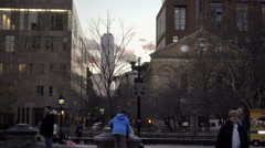 Boy climbing to top of stone at center fountain on edge of park fountain NYC Stock Footage