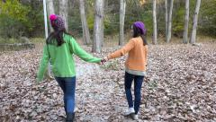 Two girls walking and having fun on autumn forest path, park, 4k steadicam sh Stock Footage