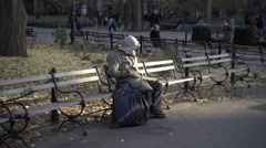 Homeless man sitting on park bench with personal items in garbage bag, cold NYC Stock Footage