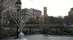 Huge Menorah in Washington Square Park, panning across trees and buildings NYC Stock Footage