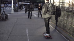 Kid on skateboard, skateboarding down street on 5th Ave in slow motion 1080 HD Stock Footage