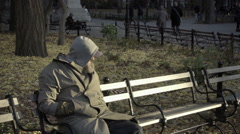 Man bundled up with hood sitting on park bench thinking, cold fall day park NYC Stock Footage