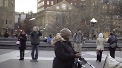 Nanny pushing baby in stroller on chilly day, Washington Square Park, New York Stock Footage