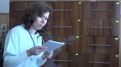 Female doctor with papers looking for medical report in drawer hospital archive Stock Footage