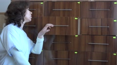 Nurse female looking for medical report in cabinet with drawers, busy office day - stock footage