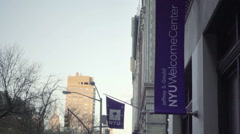 NYU Welcome Center and flag tilting down to university college students talking Stock Footage