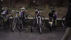 People walking by parked bicycles with purple NYU colors on breezy fall day NYC Stock Footage