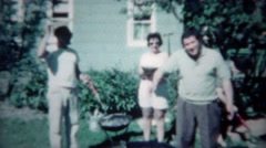 1961: Man gets dounce man grilling outdoor from sassy wife and drunk buddy. - stock footage
