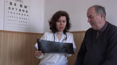 Female doctor and adult patient discussing about X-ray radiography health issues Stock Footage