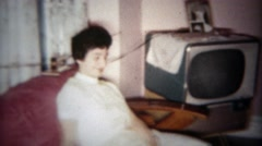 1961: Happy girl and family hanging out in front of TV in living room.  PLANO, - stock footage