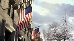 Two American flags waving over 5th Ave building in fall with changing tree in NY Stock Footage