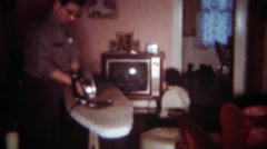 1963: Dad irons clothes in living room while daughter sits inches from TV. - stock footage