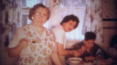 1963: Italian family eating spaghetti pasta dinner at packed kitchen table. - stock footage