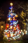 Defocused Christmas tree with star shaped bokeh lights Stock Photos