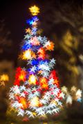 Defocused Christmas tree with star shaped bokeh lights - stock photo